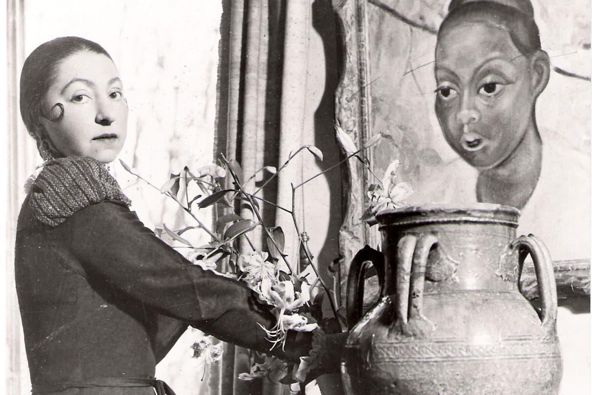 Eine Frau steht links nebe einer großen Vase und blickt in die Kamera. Rechts im Bild ist ein großes Gemälde mit einem Frauenkopf abgebildet.