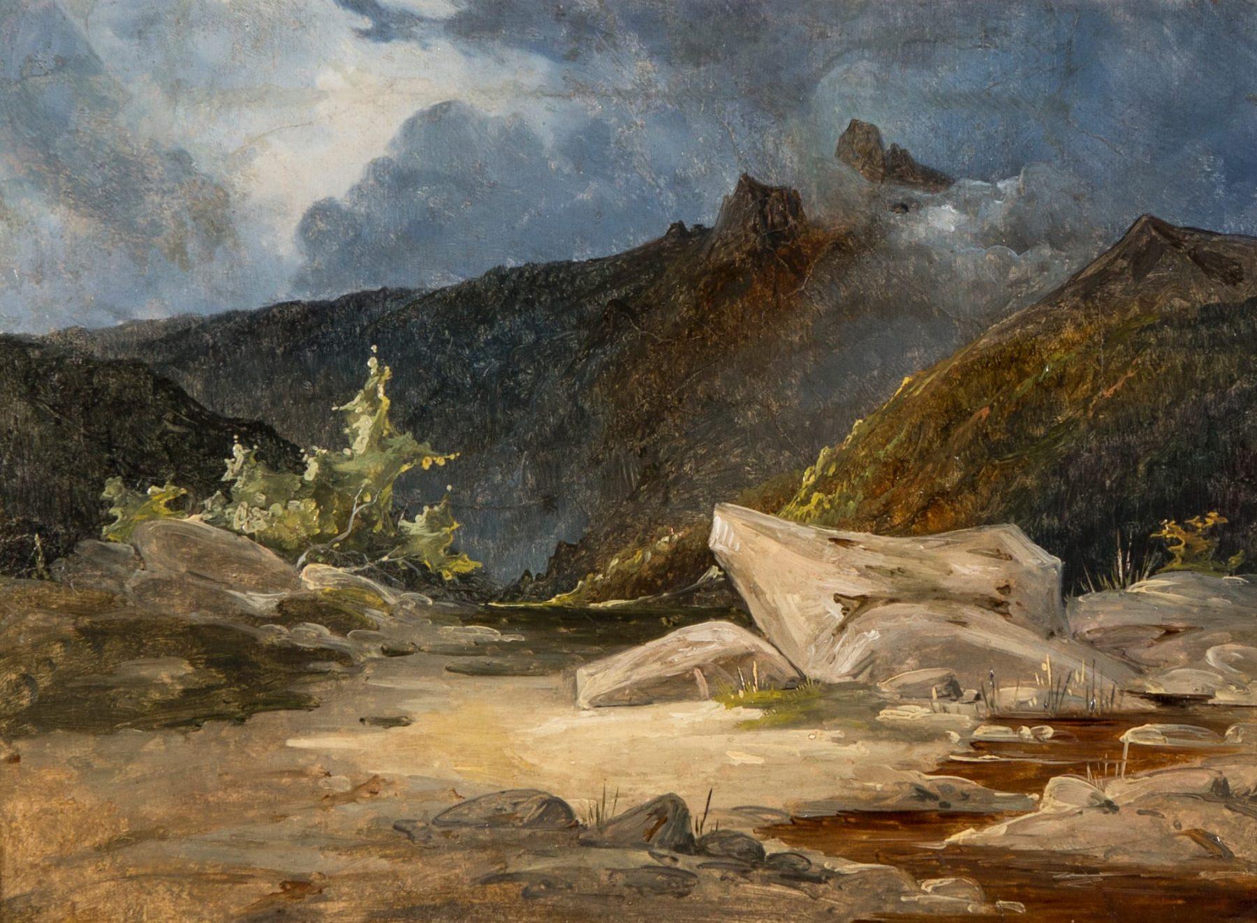 Eine hügelige Berglandschaft mit hellen Steinen im Vordergrund und einem dunklen Gebirge im Hintergrund.