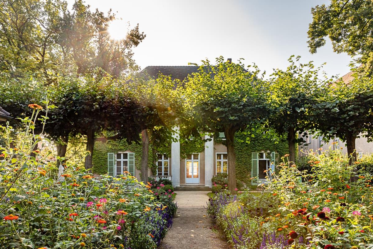 Mit Efeu bewachsene Frontseite der Liebermann-Villa mit vielen bunten Pflanzen und hohen Bäumen