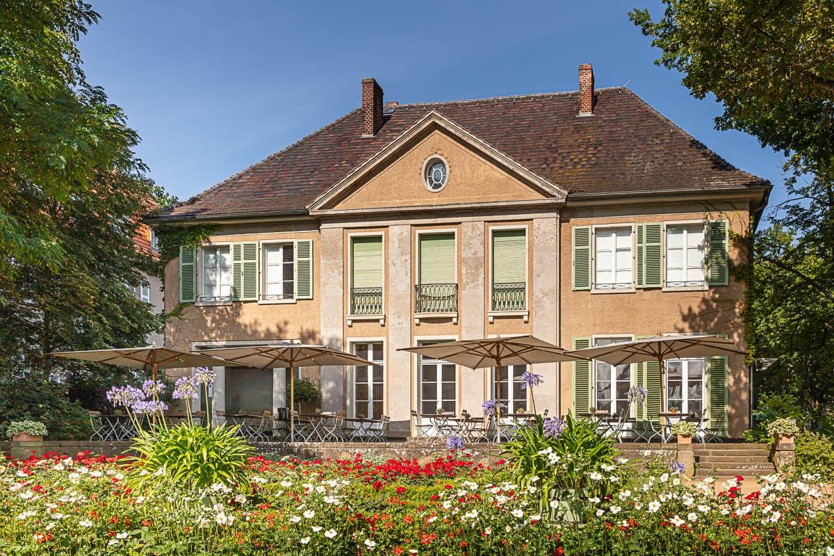 Hintere Fassade der Liebermann-Villa mit großer Terrasse und weißen, lila und roten Blumen im Vordergrund