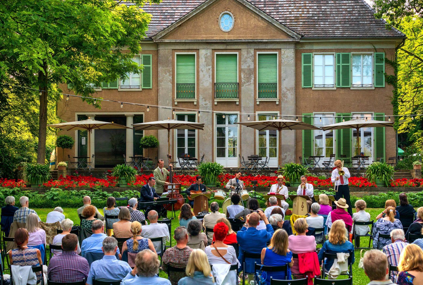 Eine große Gruppe Personen sitzt mit dem Rücken zur Kamera im Garten der Liebermann-Villa und schaut in Richtung der seeseitigen Fassade und den spielenden Musikern.
