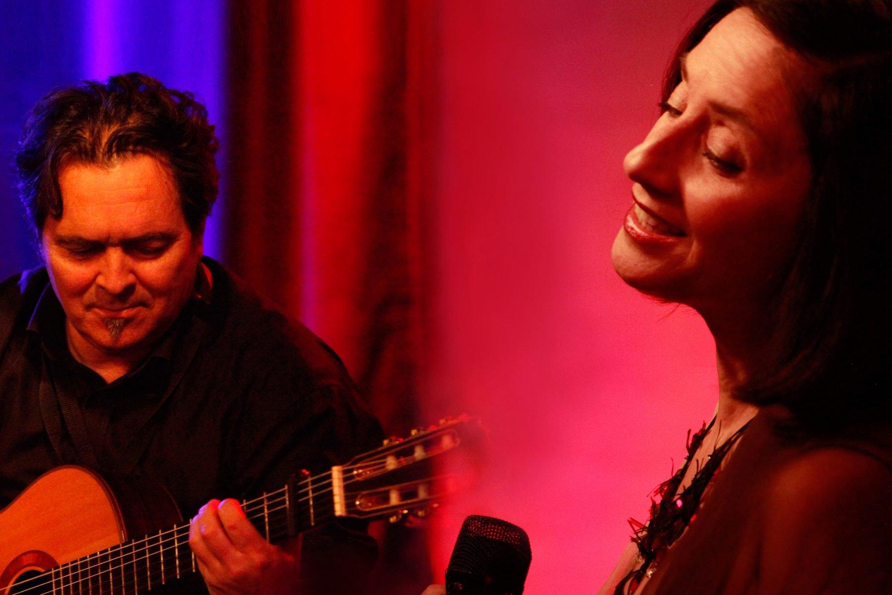 Zwei Musiker, links ein Gitarrist und rechts eine Sängerin.