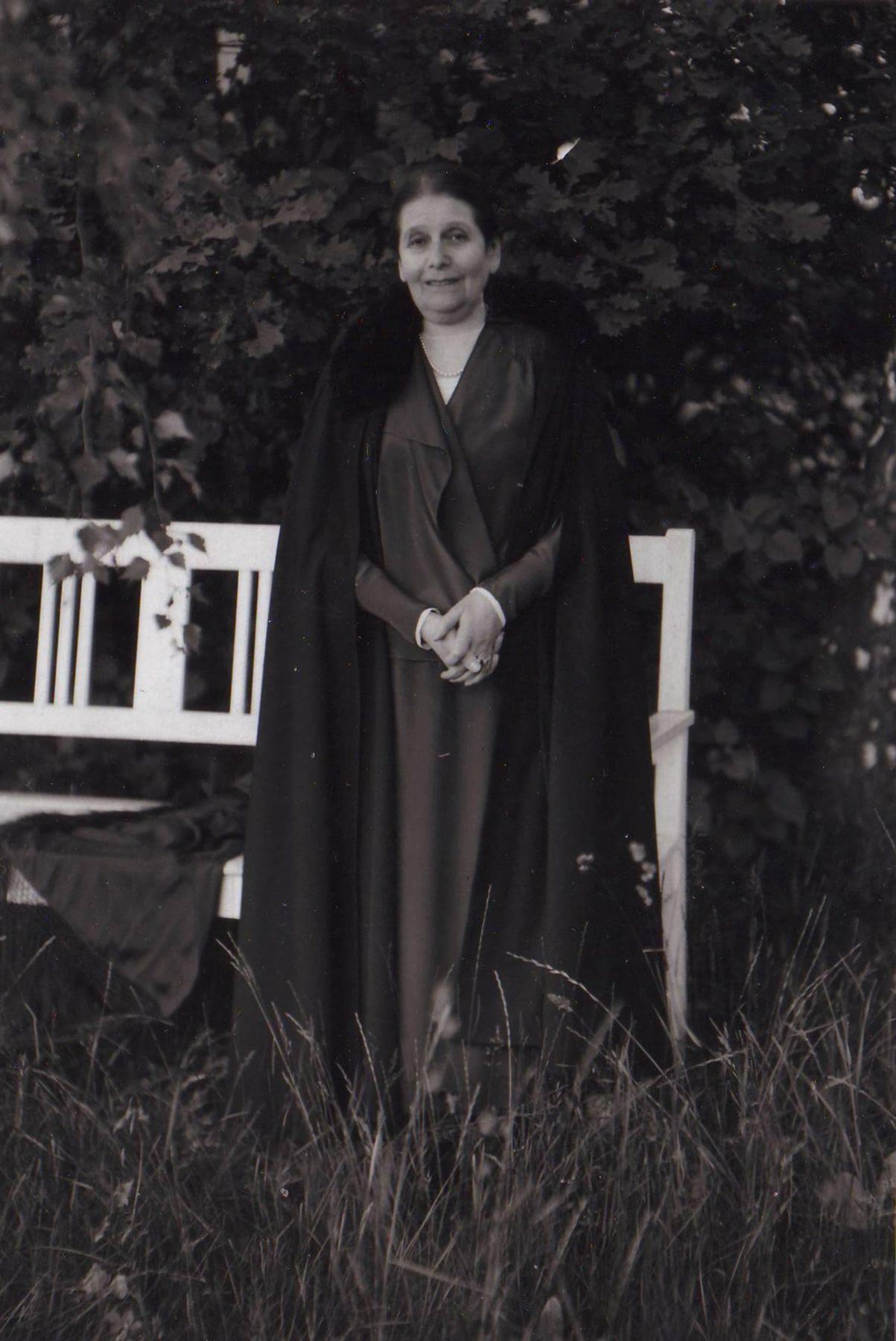 Martha Liebermann steht mit dunklen Kleidern und einem Mantel vor einer weißen Gartenbank vor einer Hecke im Garten der Liebermann-Villa