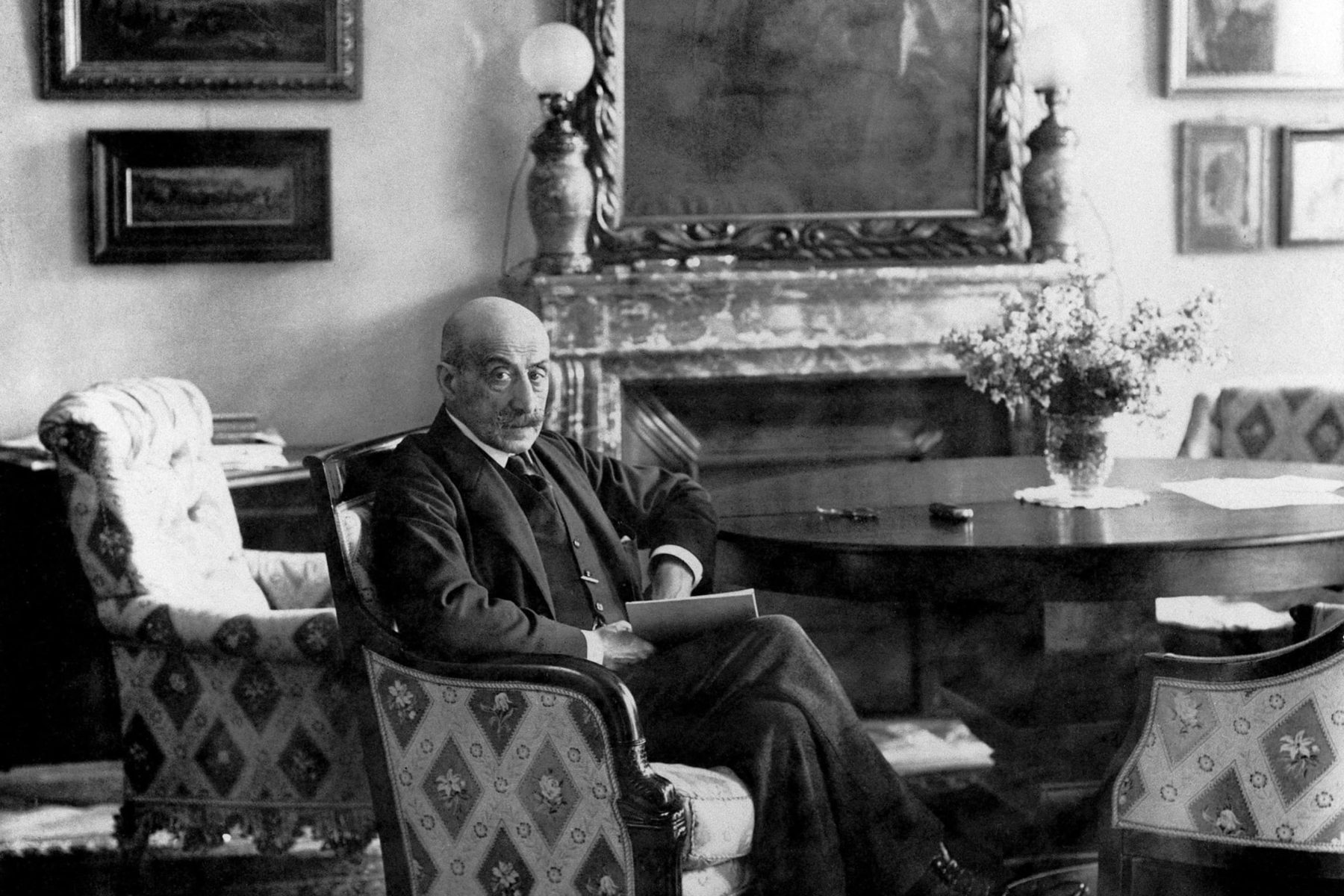Max Liebermann sitzt in seinem Kaminzimmer, seine Beine sind überkreuzt. In dem Zimmer stehen vier Sessel an einem Rundtisch, darunter liegt ein schwerer Teppich. Die Wände sind mit Gemälden behangen.