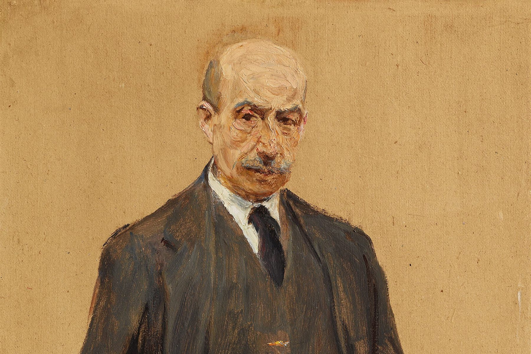 Zu sehen ist ein Selbstbildnis von Max Liebermann. Er steht im dunklen Anzug vor einem brauenen Hintergrund, die Hände in den Hosentaschen