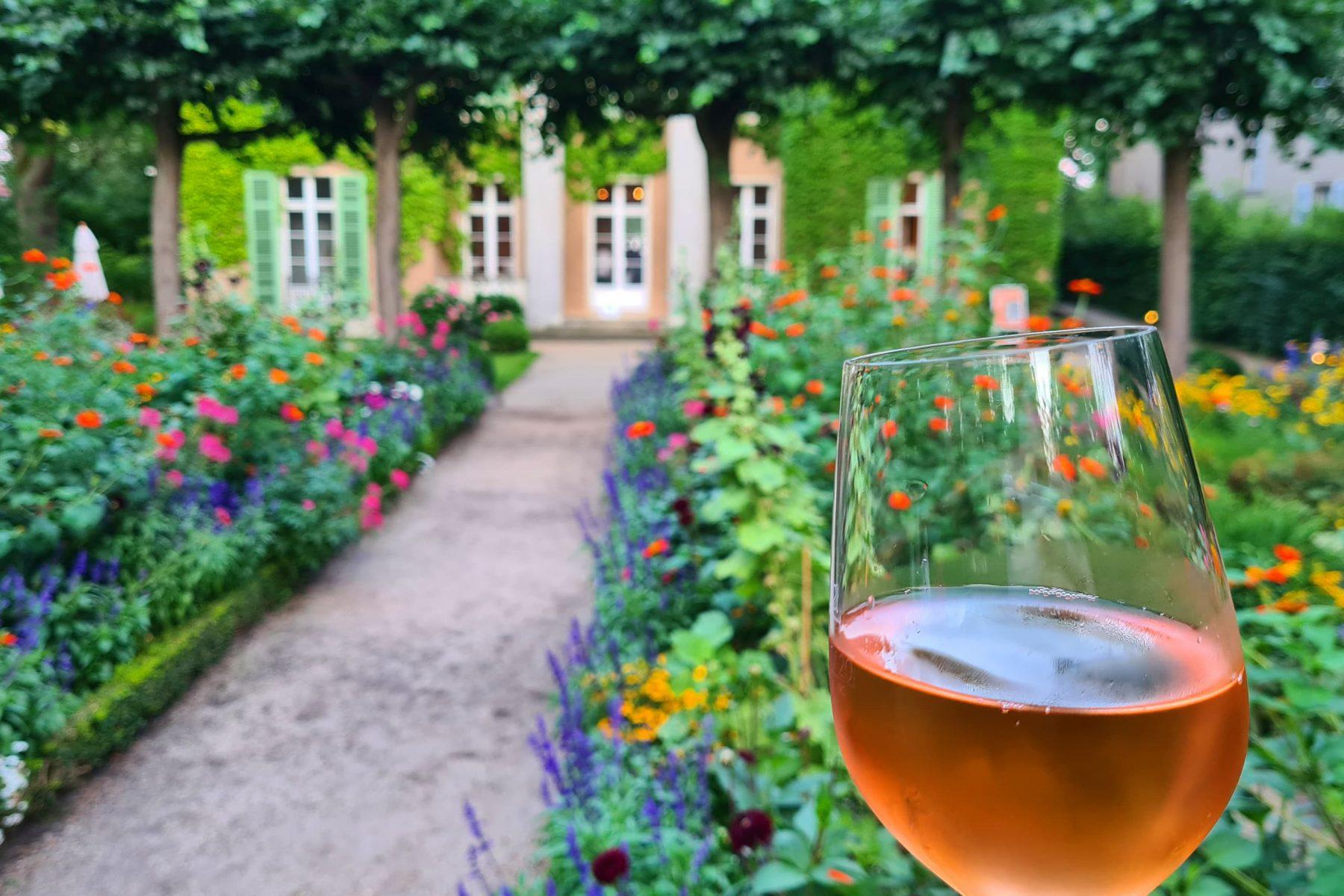 Rechts ein Weinglas mit Rosé vor der Liebermann-Villa Fassade im Hintergrund mit bunten Blumenbeeten.