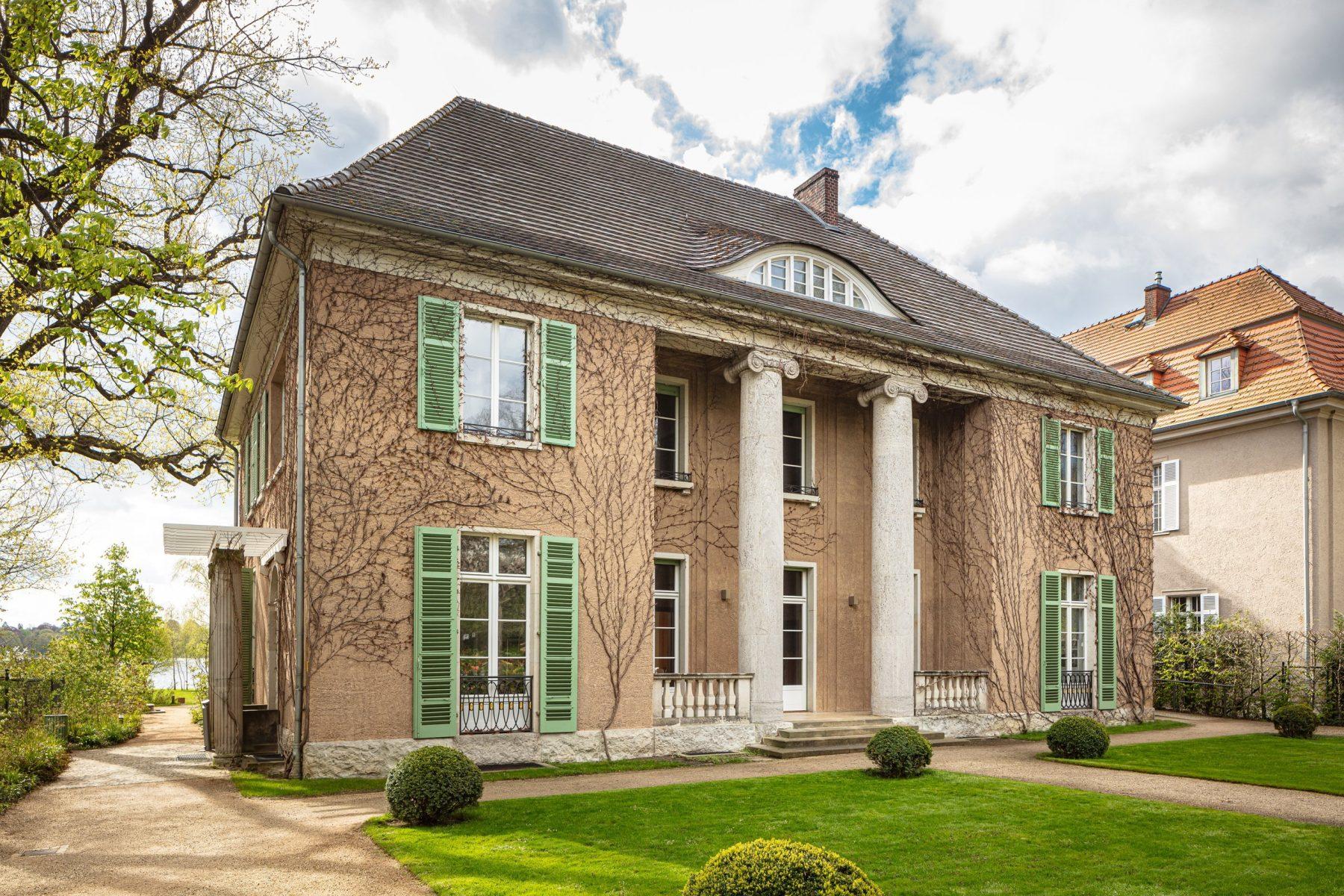 Blick auf die Frontseite der Liebermann-Villa mit grünem Rasen und einigen Buchsbäumen davor.