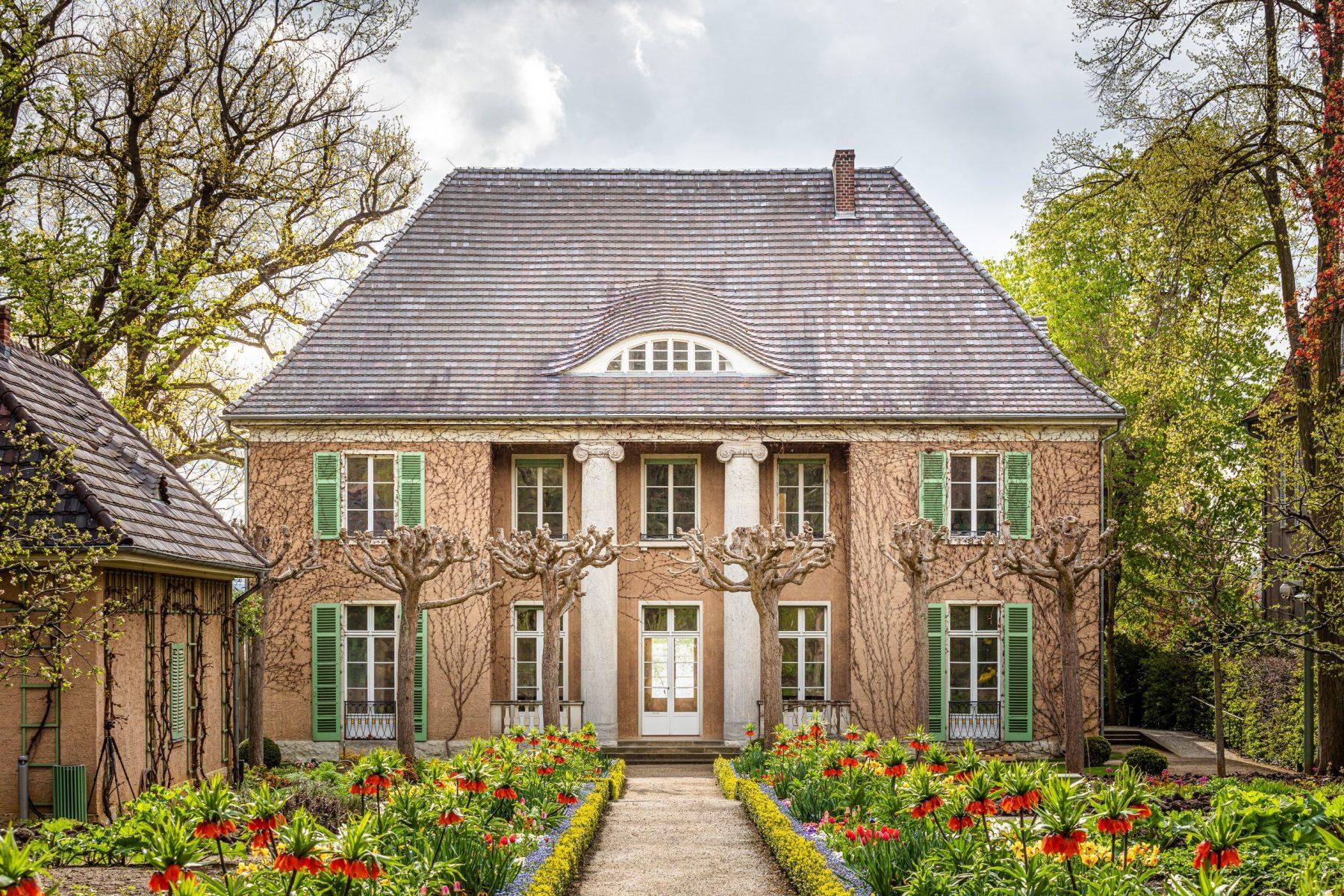Frontseite der Liebermann-Villa mit blühenden Beeten davor. Links im Bild lässt sich ein Stück des Museumsshops erkennen.