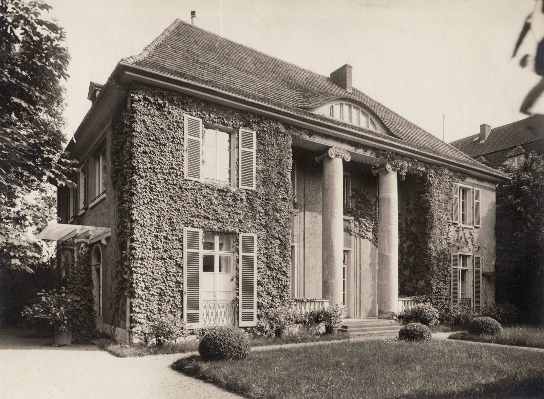 Die historische Schwarzweiß-Fotografie zeigt die mit Efeu bewachsene Frontseite der Liebermann-Villa.