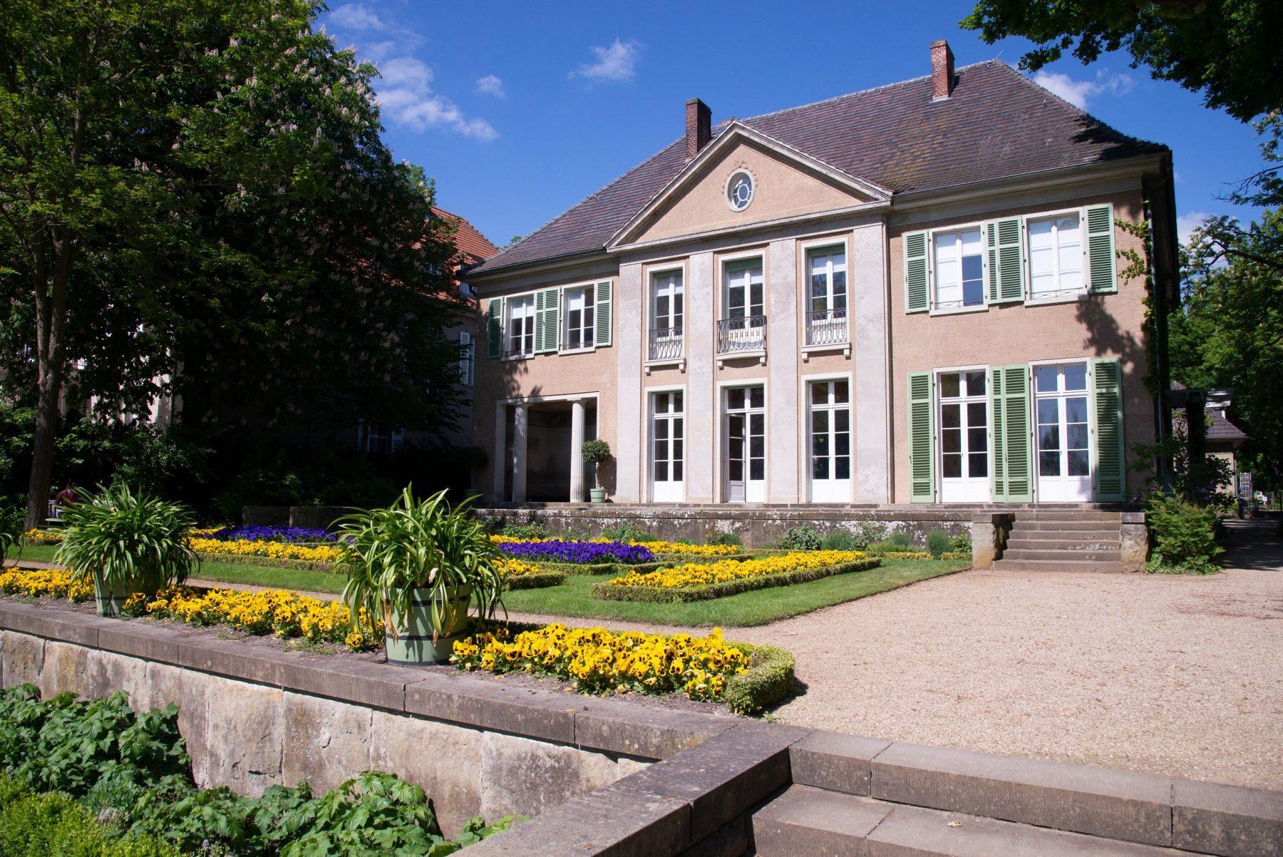 Die seeseitige Fassade der Liebermann-Villa, davor erstreckt sich die Blumenterrasse mit gelben und blauen Blumen.
