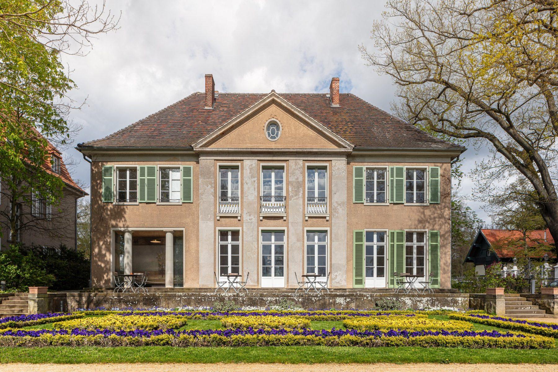 Der Blick geht auf die seeseitige Fassade der Liebermann-Villa mit gelb und violett blühenden Beeten davor.