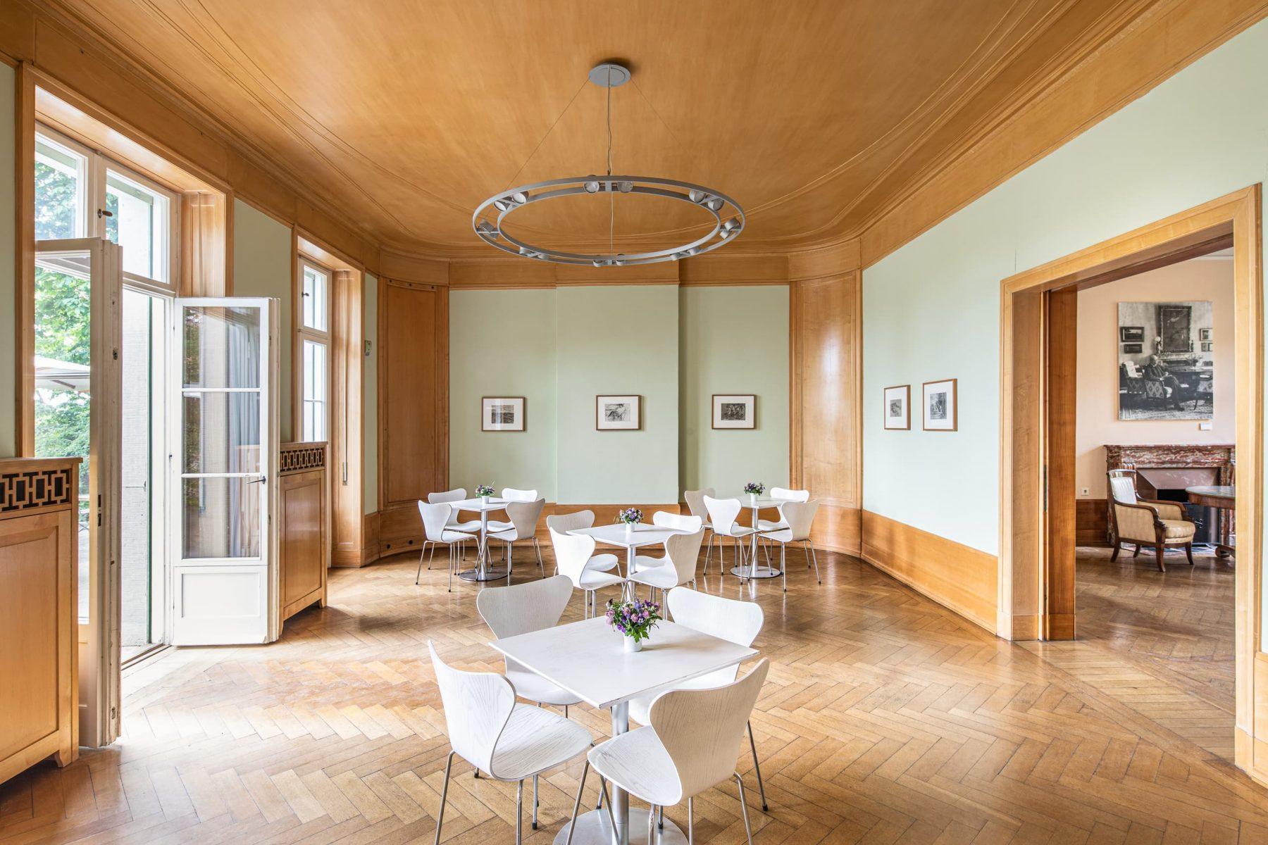 Großer Saal mit vier weißen Tischen, Stühlen und auf Holzboden. Links geöffnet Doppelfenstertüren, rechts geöffnete Schiebetüren mit Blick auf den Eingangsbereich des Museums.