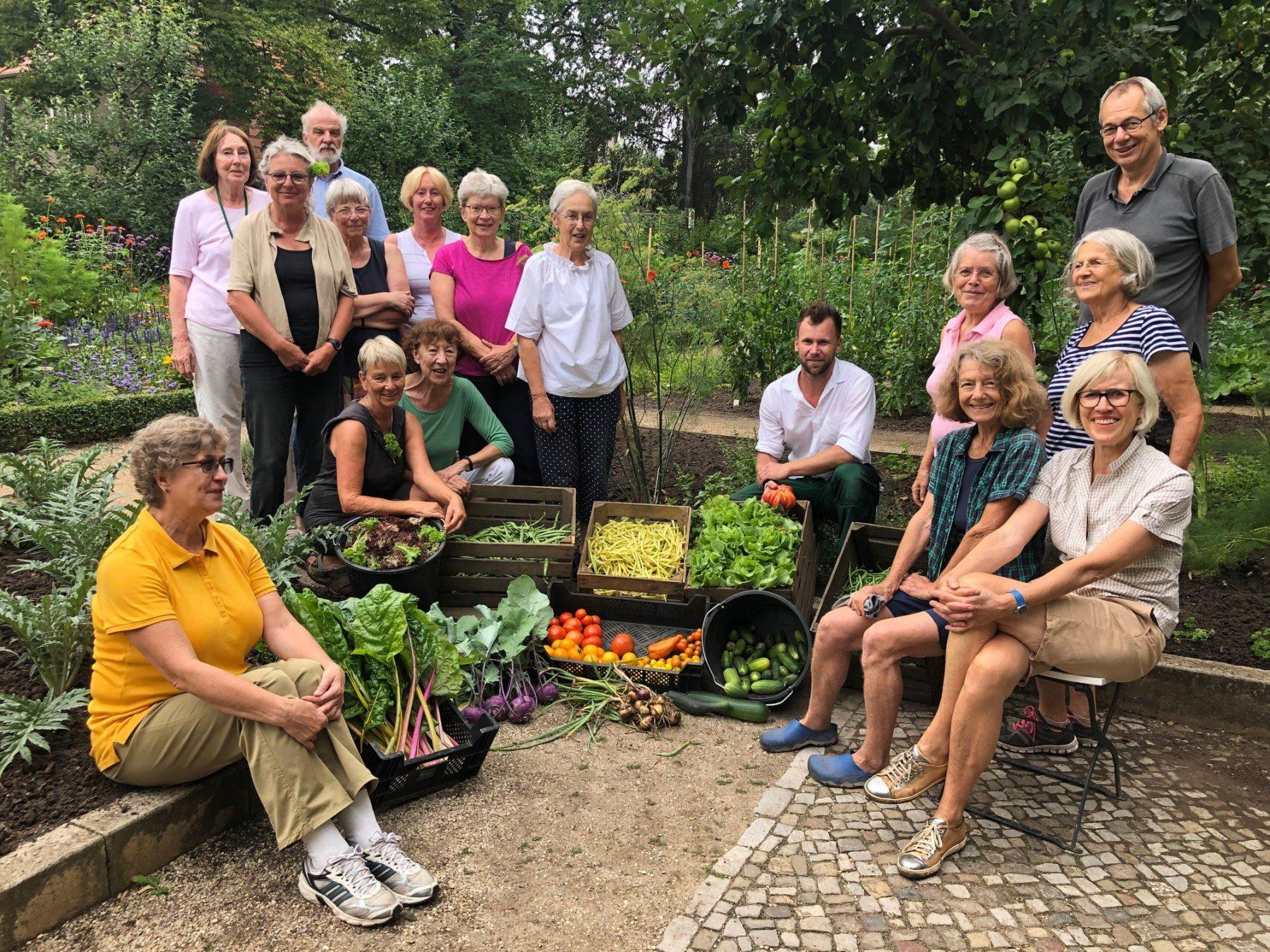 Eine Gruppe an Personen lächelt in die Kamera. Zwischen ihnen stehen einige mit Gemüse gefüllte Kisten.