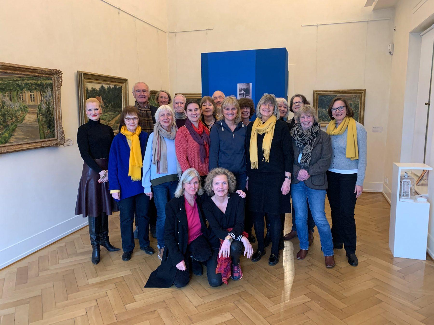 Eine große Gruppe an Personen blickt lächelnd frontal in die Kamera. Sie stehen in einem Ausstellungsrau der Liebermann-Villa.