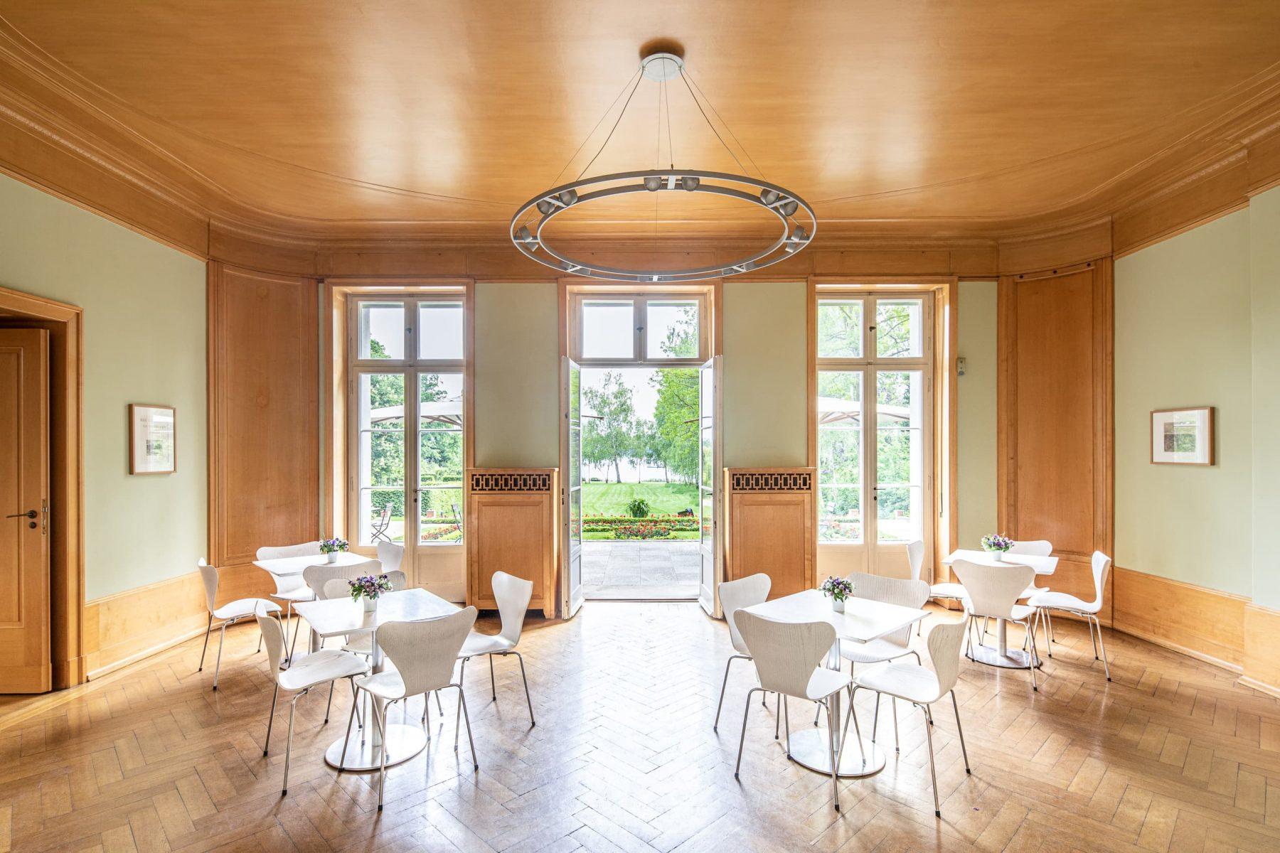 Großer Saal mit vier weißen Tischen, Stühlen und auf Holzboden. Links geöffnete Doppelfenstertüren, die den Blick auf den Wannseegarten öffnen.