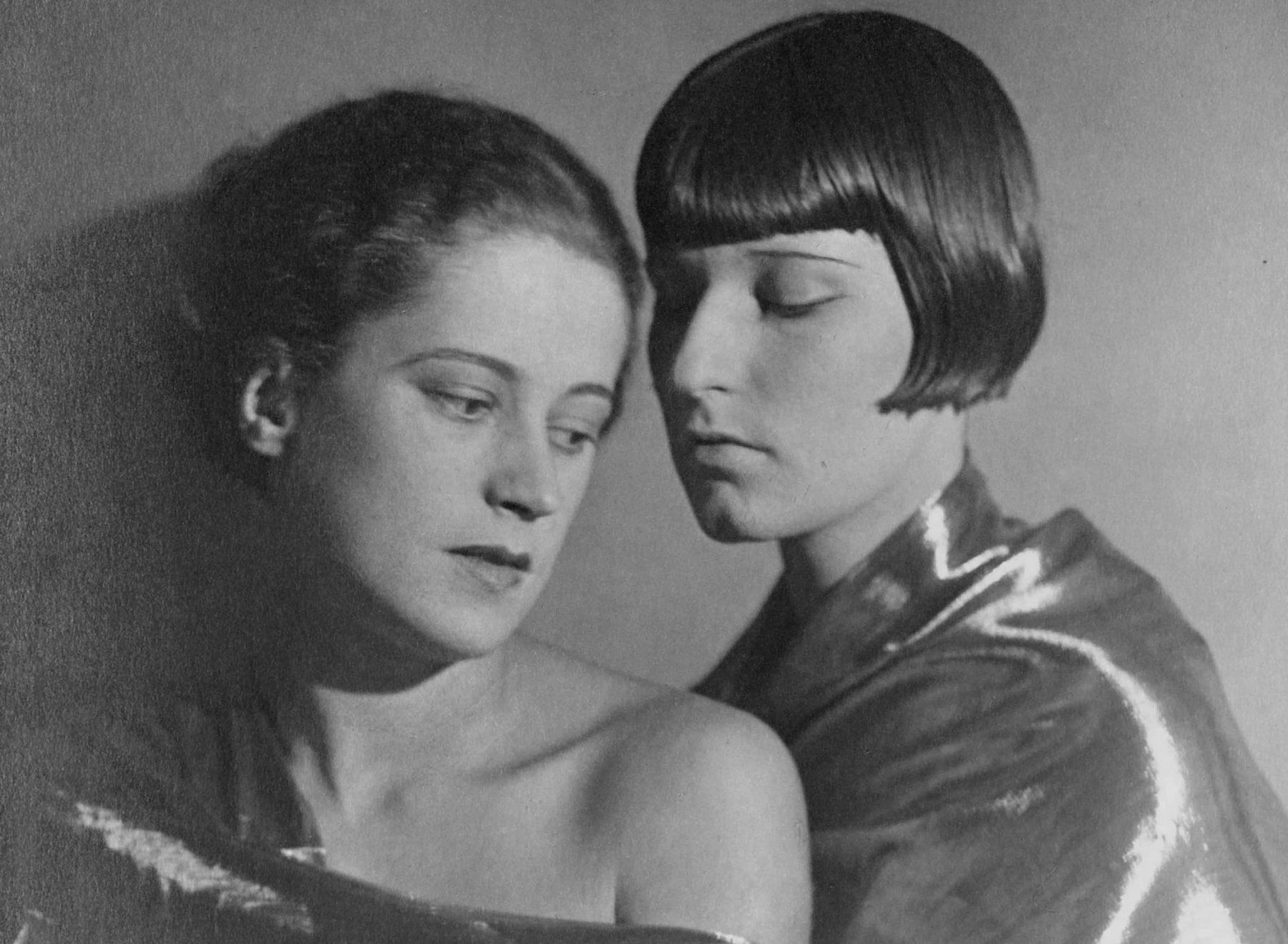 Schwarzweißfotografie von zwei jungen Frauen, die eng aneinander stehen und nach unten blicken.