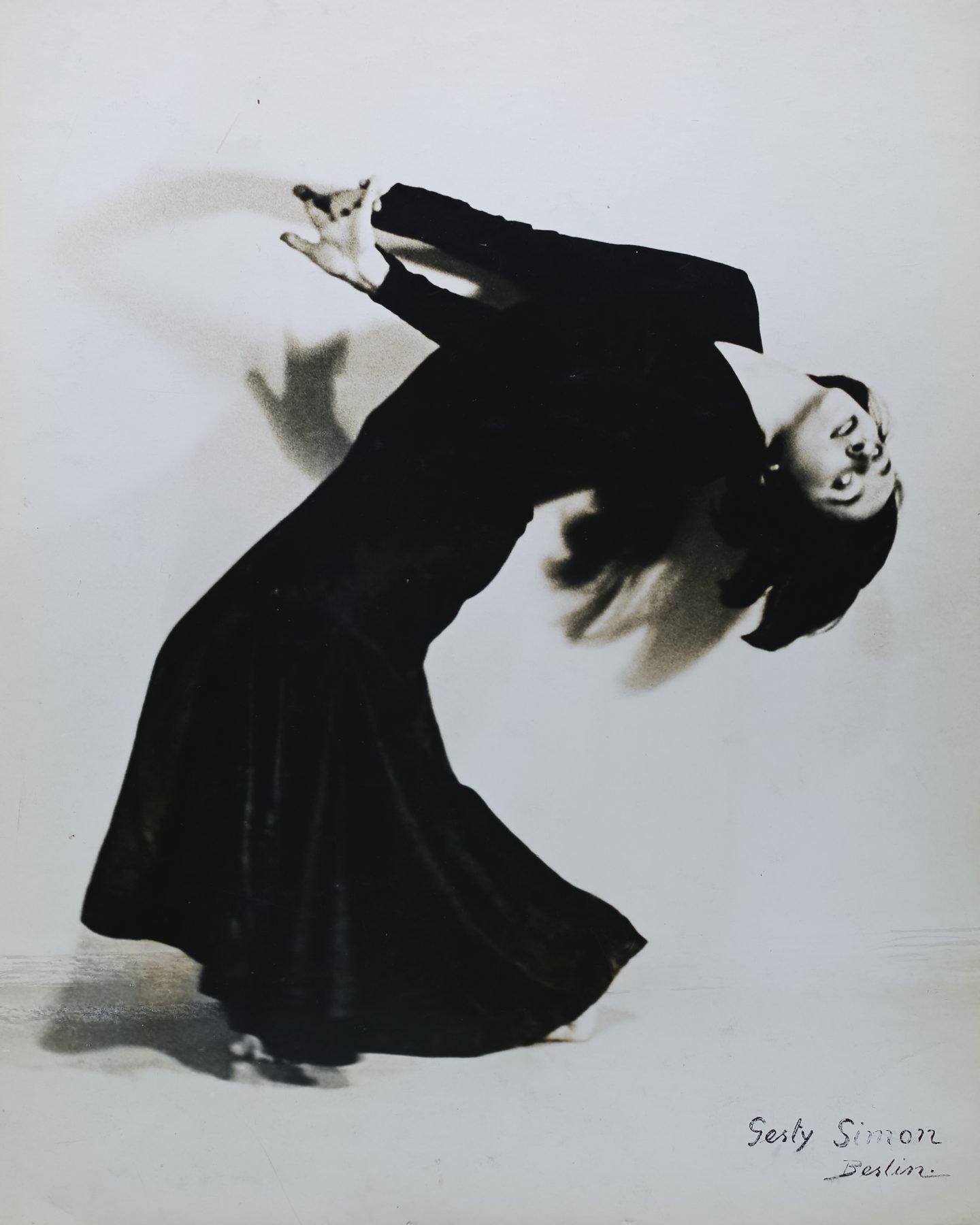 Die Tänzerin Lotte Goslar ist in einer verrenkten Körperposition zu sehen. Sie lehnt nach hinten, ihre Arme schwingen dabei nach vorn. Passend zu ihrem dunklen Haar trägt sie ein schwarzes, langes Kleid.
