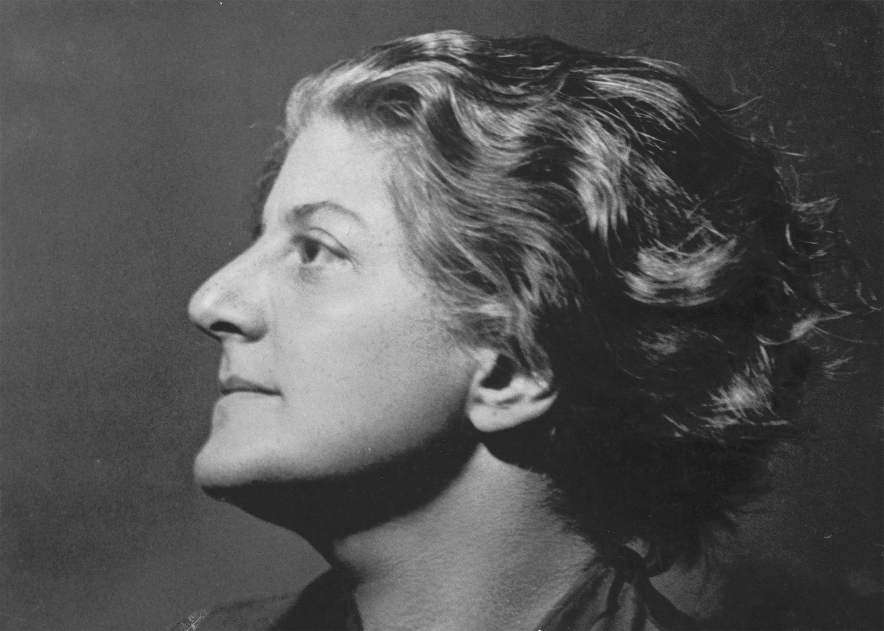 Die Abbildung zeigt ein Selbstporträt der Fotografin Gerty Simon. Ihr Kopf ist im Profil geneigt und wird durch eine von links kommende Lichtquelle angestrahlt. Ihr kurzes Haar liegt ihr in voluminösen Wellen am Kopf.