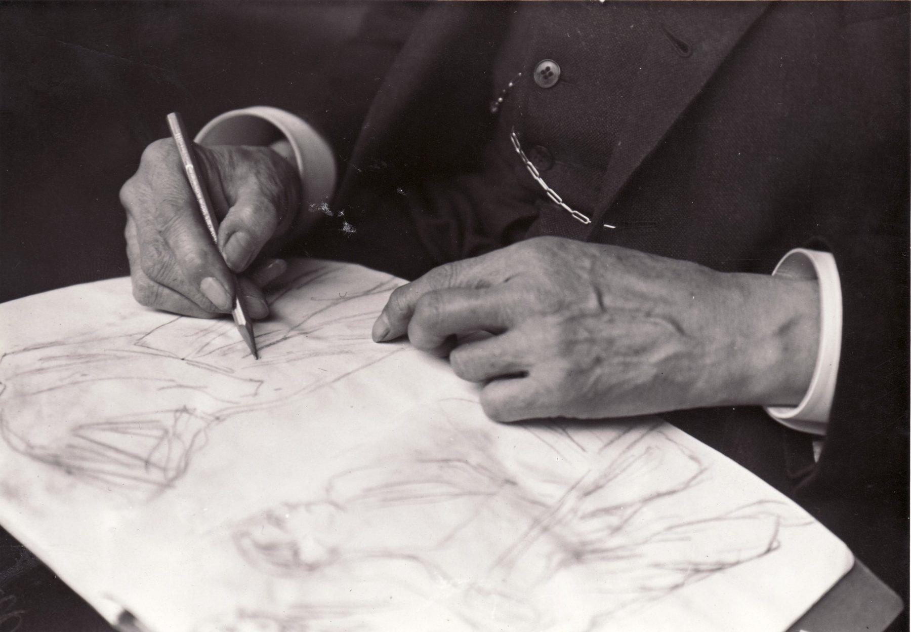 Max Liebermann zeichnet auf einem Blatt Papier. Der Fotoausschnitt zeigt nur seine Hände, in der rechten hält er einen Stift.