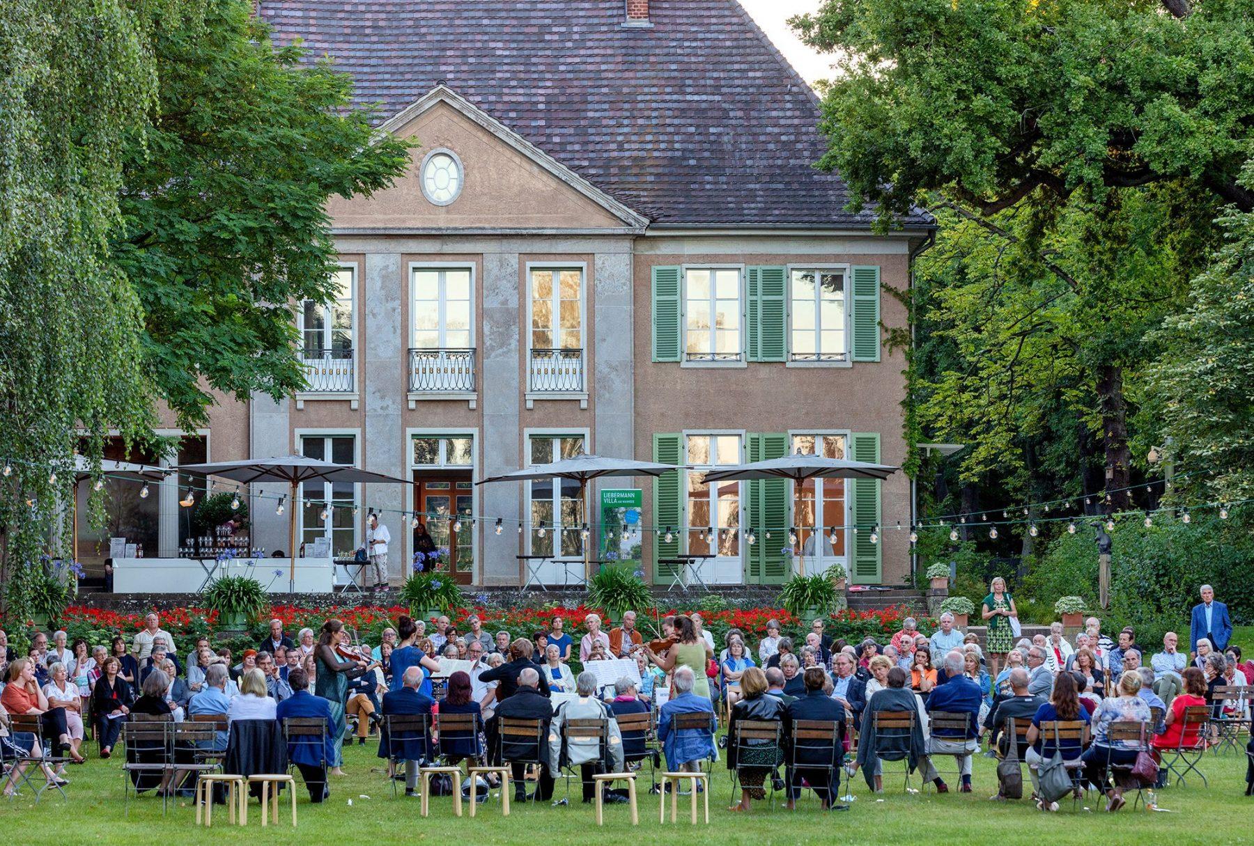 Eine große Gruppe Personen sitzt mit dem Rücken zur Kamera im Garten der Liebermann-Villa und schaut in Richtung der seeseitigen Fassade.