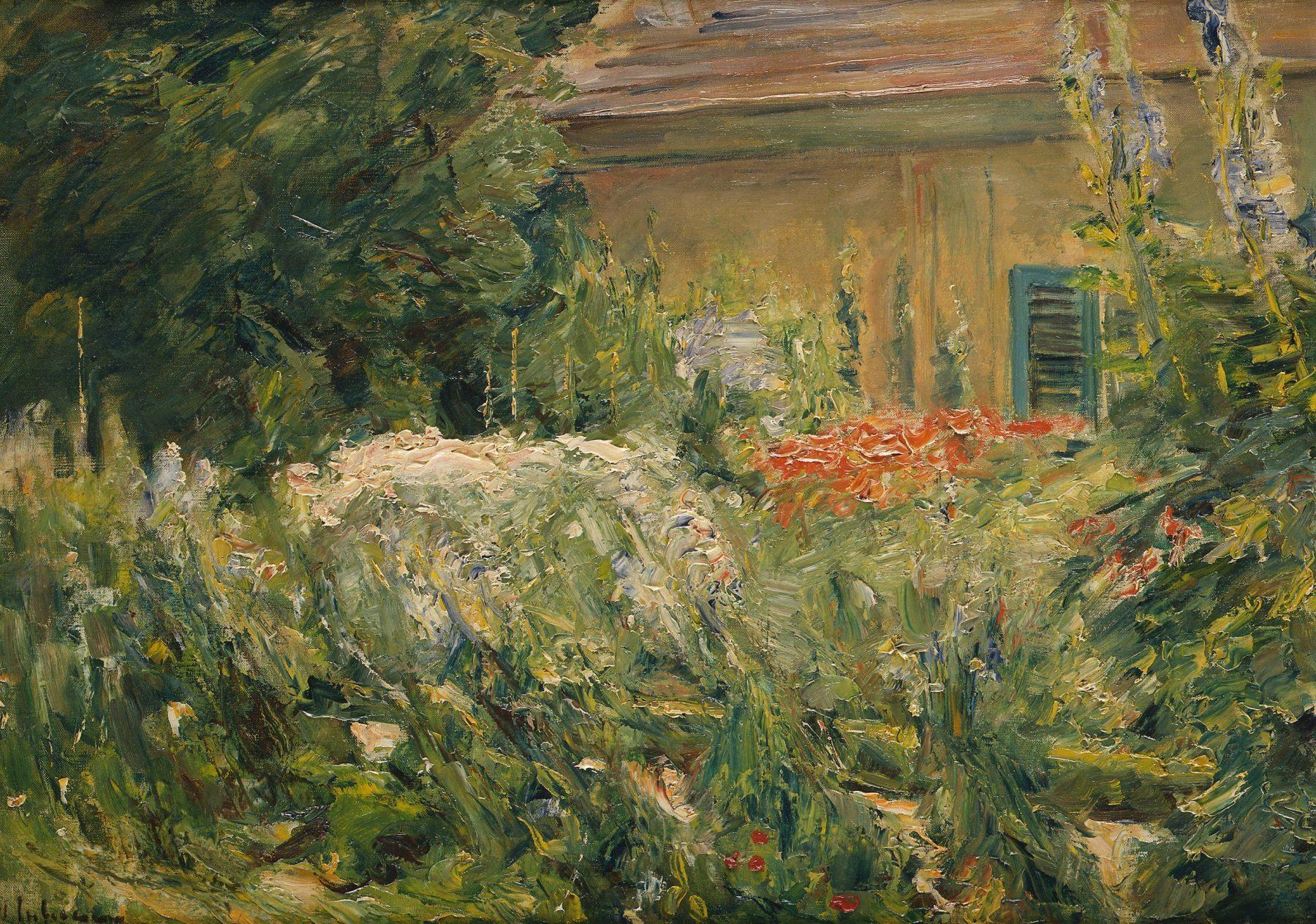 Der Blick geht Richtung Gärtnerhaus im Hintergrund mit üppigen Blumenstauden im Vordergrund.