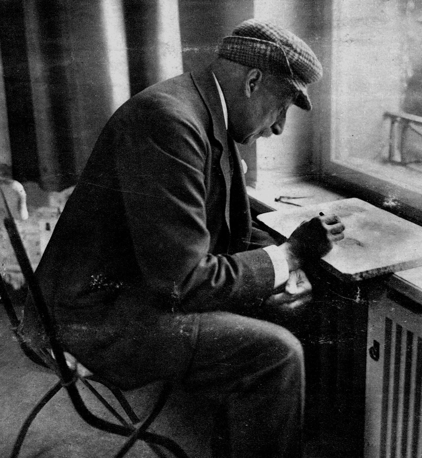 Max Liebermann sitzt an der Fensterbank seines Ateliers bei der Arbeit. Er trägt einen Anzug und eine Art Schiefermütze.