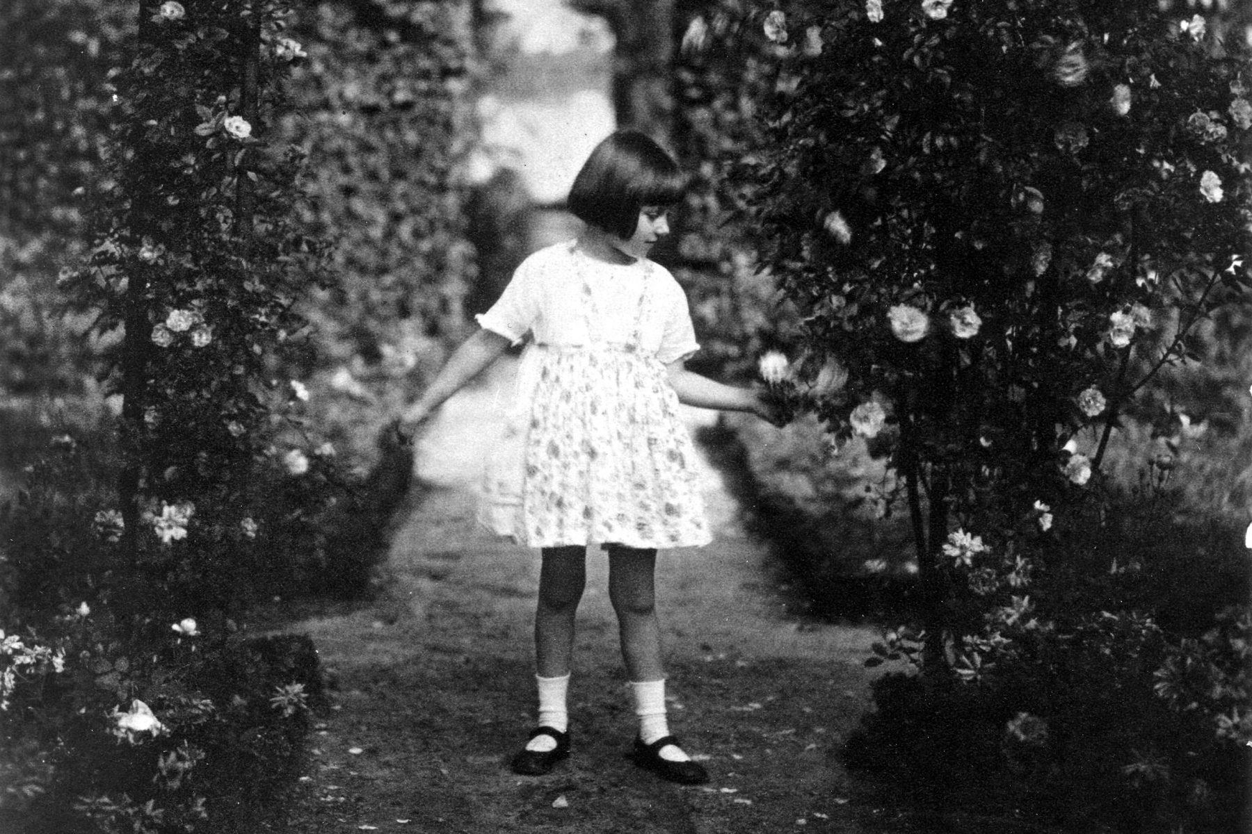 Max Liebermanns Enkelin Maria steht in einem weißen Kleid inmitten der Rosengärten. Der Blick reicht bis zum dahinter liegenden Wannsee.
